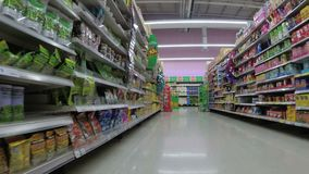 Shelves with goods in supermarket. Grocery shopping from view of a shopping cart. Thailand.