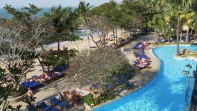 Tropical Hotel with swimming pool blue water on the beach. PATTAYA, THAILAND, DECEMBER 25, 2017: Tropical Hotel with swimming pool blue water on the beach stock video footage
