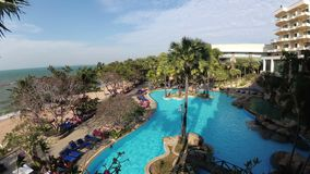 Tropical Hotel with swimming pool blue water on the beach. PATTAYA, THAILAND, DECEMBER 25, 2017: Tropical Hotel with swimming pool blue water on the beach stock footage