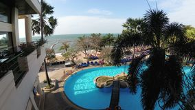 Tropical Hotel with swimming pool blue water on the beach. PATTAYA, THAILAND, DECEMBER 25, 2017: Tropical Hotel with swimming pool blue water on the beach stock video