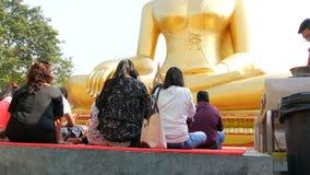 PATTAYA, THAILAND - 18. Dezember 2017: Leute sitzen und beten vor enormer Buddha-Statue Große goldene Buddha-Statue an stock video footage
