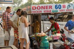 Tourists stand at a mobile stall and buy kebabs stock images