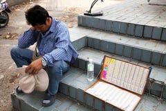 Pattaya, Thailand - 28. März 2016: Müdes Lotterieverkäufersitzen Stockbild