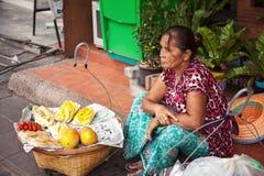 Pattaya, Thailand - 28. März 2016: Thailändischer Straßenhändler, der Früchte von den Körben verkauft Lebensmittelverkäufer Lizenzfreies Stockfoto