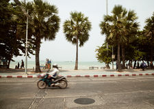 Pattaya, Thailand - 23 March, 2016: Motorcycle rider on a tropical beach road. Beautiful scenery with motorbike, sea and palm trees Royalty Free Stock Image