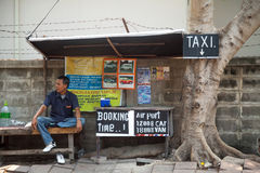 PATTAYA, THAILAND - MARCH 22, 2016: Thai taxi driver waiting for customers next to advertisement Stock Photography