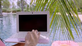 Pattaya, Thailand - May 15, 2019: Female working on her laptop, sitting by the pool. female hands on the keyboard in the stock video footage