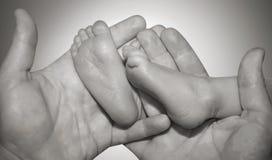 Patte de l'enfant nouveau-né dans des mains de soin Photographie stock libre de droits