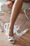 Patte de mariée dans des chaussures blanches Photos stock
