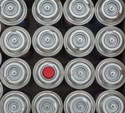 Pattern of aerosol tins arrangement. Some of aerosol tins with one that have red cap stock images