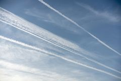 Pattern of airplane trails of condensed air crisscrossing each other against the blue sky royalty free stock photo