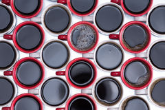 Pattern of black coffee in red and white mugs. Decorative background pattern of black coffee in red and white mugs arranged in alternating rows with all handles royalty free stock photo