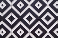 Pattern of black and white rhombuses on old doors. Elements of design in the form of geometric figures - black and white rhombuses on the ancient doors Royalty Free Stock Photos