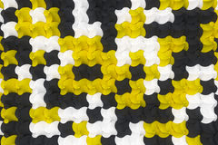 Pattern of black, white and yellow twisted pyramid shapes Stock Photos