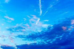 Pattern of blue, pink and white clouds, airplane trails on blue sky stock photography