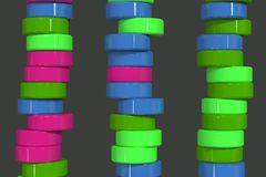 Pattern of blue, red and green cylinder tablets on black background. Plastic pucks. Abstract background. 3D rendering illustration Royalty Free Stock Photo