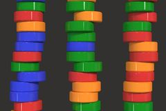 Pattern of blue, red and green cylinder tablets on black background. Plastic pucks. Abstract background. 3D rendering illustration Stock Photo