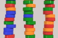 Pattern of blue, red and green cylinder tablets on white background. Plastic pucks. Abstract background. 3D rendering illustration Stock Photography