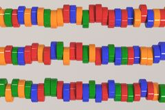 Pattern of blue, red and green cylinder tablets on white background. Plastic pucks. Abstract background. 3D rendering illustration Stock Photos