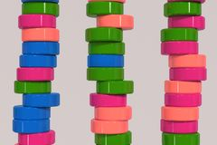 Pattern of blue, red and green cylinder tablets on white background. Plastic pucks. Abstract background. 3D rendering illustration Royalty Free Stock Image