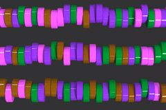 Pattern of brown, violet and green cylinder tablets on black bac. Kground. Plastic pucks. Abstract background. 3D rendering illustration Royalty Free Stock Images