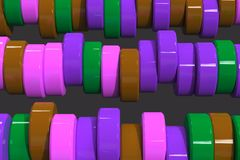 Pattern of brown, violet and green cylinder tablets on black bac. Kground. Plastic pucks. Abstract background. 3D rendering illustration Royalty Free Stock Image