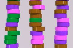 Pattern of brown, violet and green cylinder tablets on white bac. Kground. Plastic pucks. Abstract background. 3D rendering illustration Royalty Free Stock Photography
