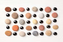 Pattern of colored pebbles and black glass beads on white wooden background. Flat lay, top view stock photography