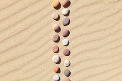 Pattern of colored pebbles on clean sand. Zen background, harmony and meditation concept. Pattern of colored pebbles on clean sand. The concept of peace and stock photo