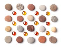 Pattern of colored pebbles and orange glass beads isolated on white background. stock image