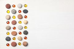 Pattern of colored pebbles and orange glass beads on white wooden background. Flat lay, top view. Pattern of colored pebbles and orange glass beads on white Royalty Free Stock Image