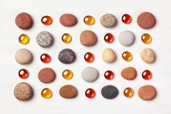Pattern of colored pebbles and orange glass beads on white wooden background. Flat lay, top view. Pattern of colored pebbles and orange glass beads on white Stock Image