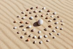 Pattern of colored pebbles in the shape of a circle on clean sand royalty free stock photography