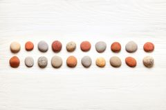 pattern of colored pebbles on white wooden background. Flat lay, top view royalty free stock photos