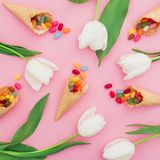 Pattern of colorful bright candy in waffle cones and white flowers on pink background. Flat lay, top view. Pattern of colorful bright candy in waffle cones and royalty free stock photos