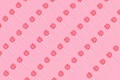 Pattern of colorful lollipop candy with stick on soft pink background. Flat lay stock photos