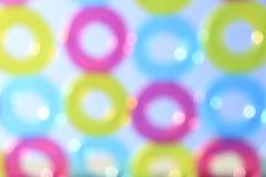 Pattern of colorful pool rings against blue sky - Defocus bokeh Stock Images