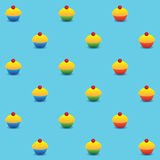 Pattern cupcakes blue background. Vector seamless pattern. Yellow cupcakes with red cherry on the top in colorful cups. Square format, light blue background Royalty Free Stock Images