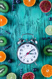 Pattern cut citrus, lavender, blueberry, clock blue desk background top view mockup Royalty Free Stock Image
