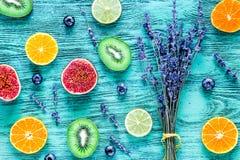 Pattern cut citrus, lavender bouquet, blueberry on blue desk background top view Stock Photos