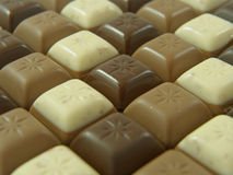 Pattern of dark, milk and white chocolate pieces stock images