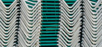 Pattern of deckchairs stacked on a pile summer season beach holiday background royalty free stock photography