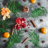 Pattern of delicious garnet, mandarin. cinnamon, anise and winter tree on dark background. Christmas concept. Flat lay. Top view Stock Image