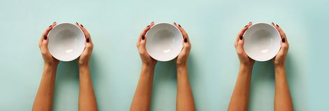 Pattern of female hand holding white empty bowl on blue background with copy space. Healthy eating, dieting concept. Banner royalty free stock photo