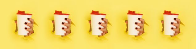 Pattern of female hand holding white paper mug on yellow background. Take away coffee cup concept. Mock up with copy space stock photos