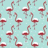 Pattern with flamingo in hat under snow on blue background. royalty free illustration