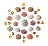 Pattern in the form of a circle of colored pebbles and orange glass beads isolated on white background. stock image
