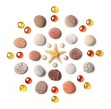 Pattern in the form of a circle of colored pebbles, starfish and orange glass beads isolated on white background royalty free stock photo