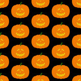 Pattern with frightful pumpkin. Seamless pattern with frightful orange colored Halloween pumpkin with evil face isolated on dark black background. For holiday Royalty Free Stock Photos