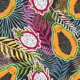 Pattern of fruits papaya and pitaya on the color of the tropical leaves. On a black background. Stock Photo
